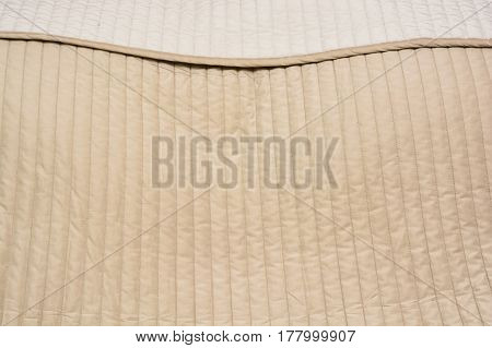 Closeup texture of lined material of beige bedcover background