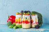 Cous cous with vegetables: bell pepper cucumber cherry tomatoes and yogurt in mason jar on blue background poster