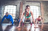 Group of sportive people training in a gym - Multiracial group of athletes doing push ups poster