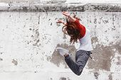 Fitness sport girl in fashion sportswear jumping and dancing hip hop by the street wall, outdoor sports, urban style poster