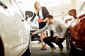 Professional salesperson selling cars at dealership to buyer poster