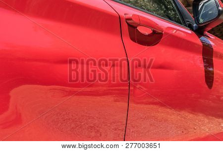 Close-up Of Dented Red Car Door After Car Accident