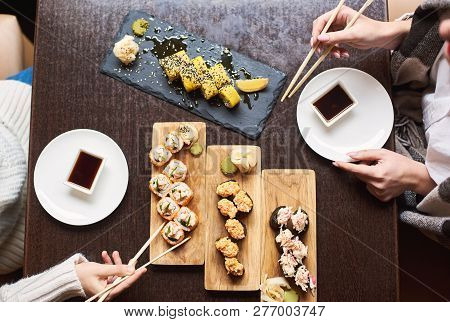 Friends Coming To Oriental Restaurant For Lunch. Women Enjoying Sushi Set With Soy Sauce, Wasabi And
