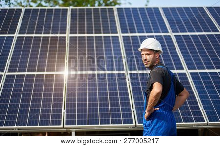 Engineer Technician On Background Of High Exterior Solar Panel Photo Voltaic System Shiny Big Blue S