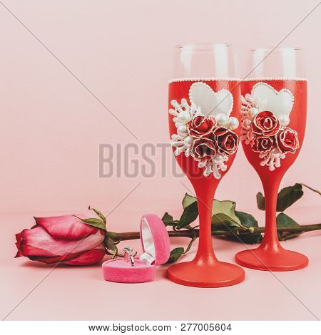 Stemware, Ring In Box And Rose On Pink Background. Decorative Decorated Wine Glasses