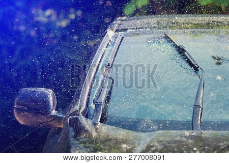 Car Windshield With Rain Drops And Frameless Wiper Blade