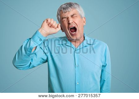 Photo Of Tired Grey Haired Retired Man Feels Sleepy, Yawns As Feels Tired, Opens Mouth Widely, Dress