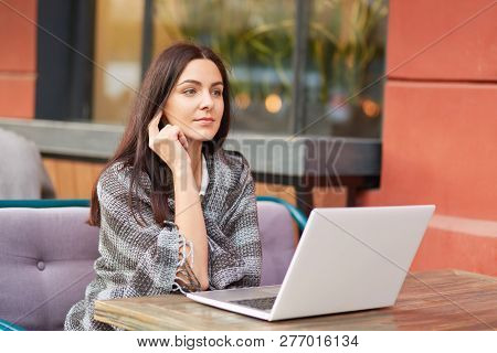 Pensive Dark Haired Woman Wrapped In Coverlet, Uses Electronic Gadget, Watches Webinar Or Surfes Soc