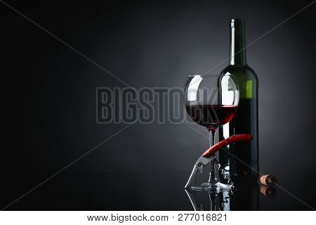 Glass And Bottle Of Red Wine With Corkscrew On A Black Reflective Background. Copy Space For Your Te