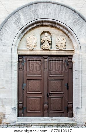 Old Door Of A Historical Building With Statues And Coats Of Arms Made Of Stone
