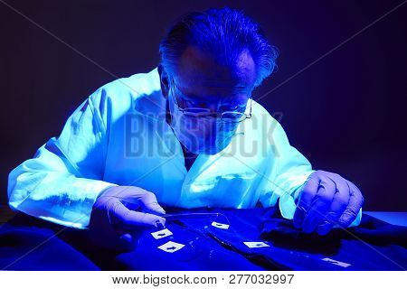 Checking Of Suspected Person Dress By Forensic Specialist In Crime Lab