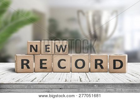 New Record Sign On A Wooden Table In A Bright Room With Green Plants And A Trophy