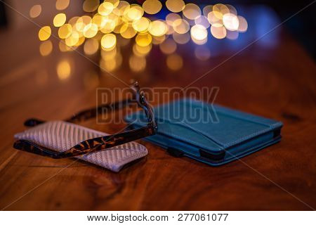 E-reader And Reading Glasses Placed On A Walnut Table With Defocused Background And Fairy Lights.
