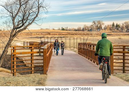 Fort Collins, CO, USA - December 25, 2019 - People are biking and walking on a newly constructed trail in Fort Collins on a Christmas Day afternoon,  a typical winter scenery without snow in Colorado.