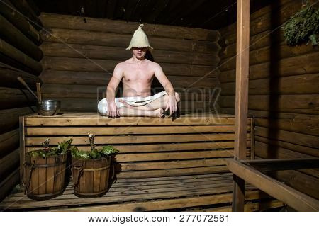 Man in a wooden Russian bathhouse and buckets with brooms poster