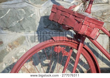 Bicycle Wheel And Wooden Basket Against Wall.