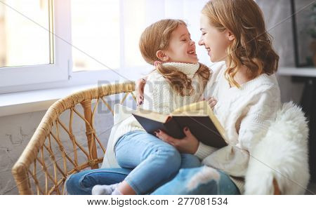 Happy Family Mother Reads Book To Child To Daughter By Window In Winter Morning