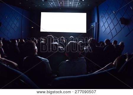 People In The Cinema Watching A Movie. Blank Empty White Screen