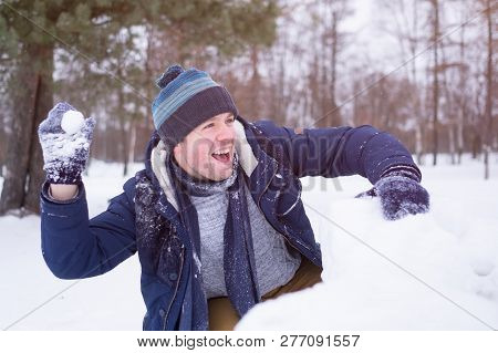 European Mature Man In Warm Clothes Playing With Snow Outdoor