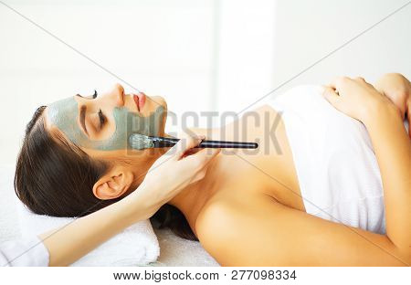 Beautiful Woman With Cosmetic Mask On Face. Girl Gets Treatment In Spa Salon Against White Backgroun
