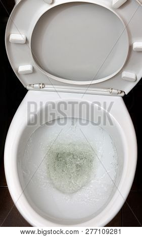 A Photo Of A White Ceramic Toilet Bowl In The Process Of Washing It Off. Ceramic Sanitary Ware For C