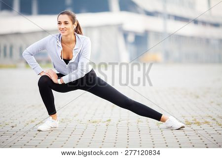 Fitness. Woman Doing Stretching Exercise On Stadium Background