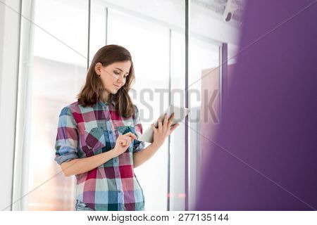 Young businesswoman using digital tablet in office