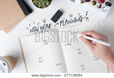 Top View Of Hand Writing  New Year's Planning On Open Calendar Planner With Doodle Style For Life Re