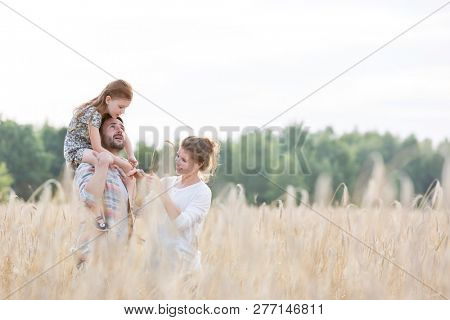Happy family standing amidst wheat crops at farm against sky