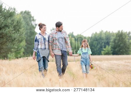 Family walking on grassy field against sky at farm