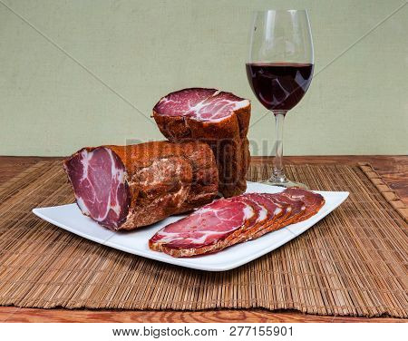 Partly Sliced Dried Pork Neck On The Square White Dish And Glass Of Red Wine On Bamboo Table Mat On
