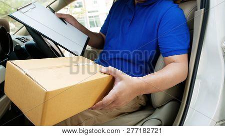 Deliverer Sitting In A Van Holding A Box