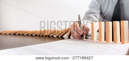 Chain Reaction In Business Concept, Businessman Intervening Chain Dominoes Toppling By Signing A Con