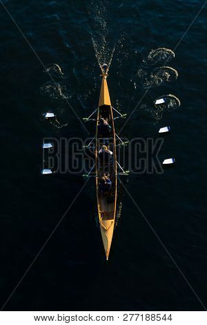 Close-up Of A Powerful Rowing Team In A Rowing Boat. View From Above Of A Floating Rowing Boat With