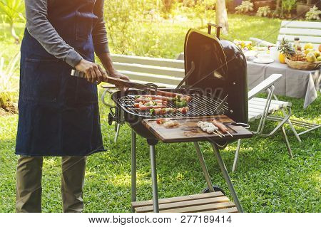 Handsome Man Preparing Barbecue For Friends In The Garden.- Image