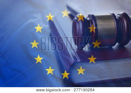 Judgement gavel on the code of European Union laws, with EU flag as a full frame legal system background concept poster