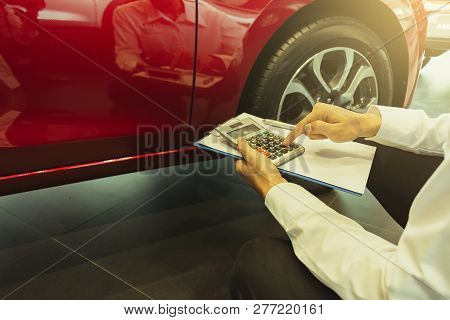 This Career Salesman Calculating On Calculator Car Price In Showroom Car.close Up Tire Red Car In De