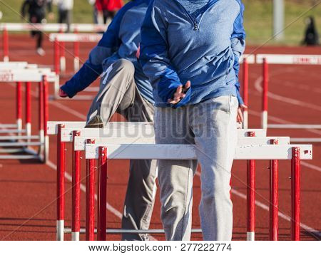 Two High School Girls Doing Hurdle Walk Over Drills In The Sweats While Warming Up For To Run In The