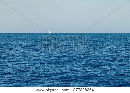 A Lone White Sailing Yacht Sails In The Waters Of The Mediterranean
