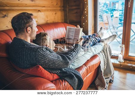 Father And Son Reading Book Together Lying On The Cozy Sofa In Warm Country House. Reading To Kids C