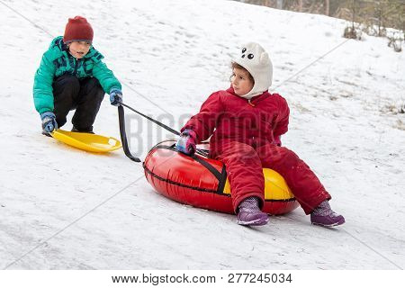 Brother Pulls Sister On Sled On The Hill
