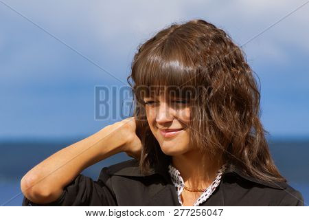 Closeup Portrait Of Beautiful Smiling Woman In Black Jacket, With Long Dark Brown Curly Hair Outdoor