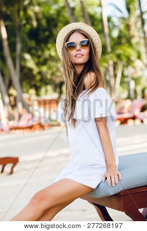 Cute Girl In Brown Sunglasses And Straw Hat Smiles Charmingly. She Wears White Short Dress With Open