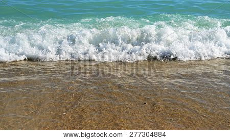Ocean Water Splashing Onto The Shore Background.