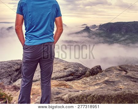 Sports Figure Casual Man Wearing Outoor Clothes And Boots Walking On Rocky Peak On A Sunny Fall Day