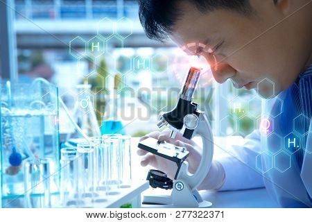 Medical Research Scientists Looking Through A Microscope In A The Forensic Laboratory