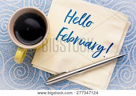 Hello February - handwriting on a napkin with a cup of coffee against lace paper