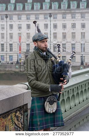 London, United Kingdom - November 23, 2018: Street Musician Scotsman Playing The Bagpipes On The Wes