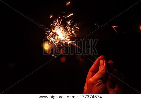 New year party burning sparkler closeup in male hand on unsharp dark background. man holds glowing holiday sparkling hand fireworks
