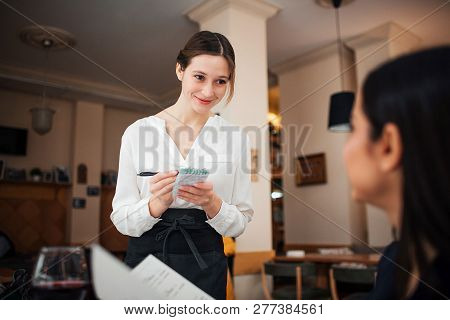 Cheerful Young Waitress Stand In Front Of Customer. She Write Order. Waitress Look At Customer And S